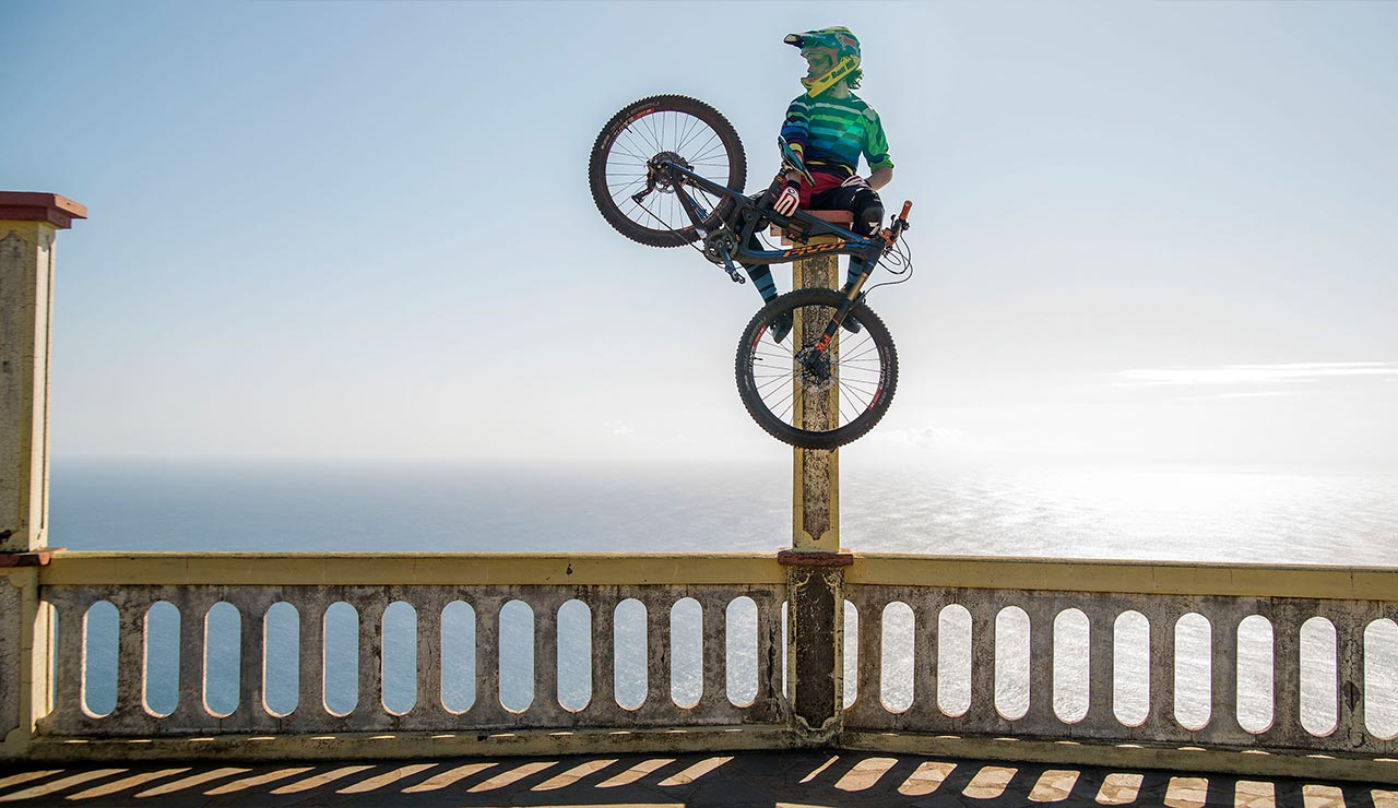 Bam Hill's sitting on a large pillar, bike in hand, overlooking the ocean.