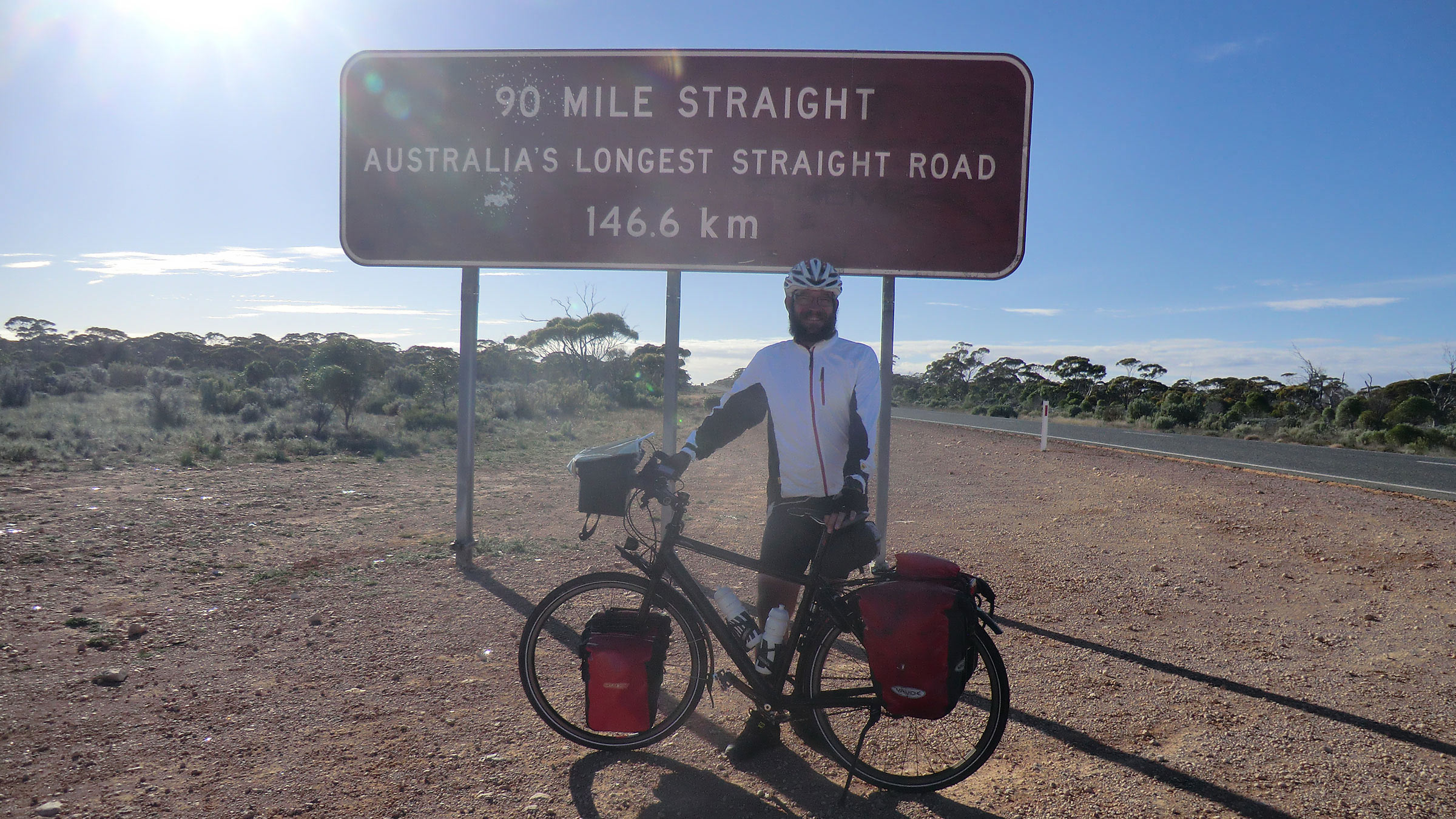 Frank in front of a sign that announces Australia's longest straight road.