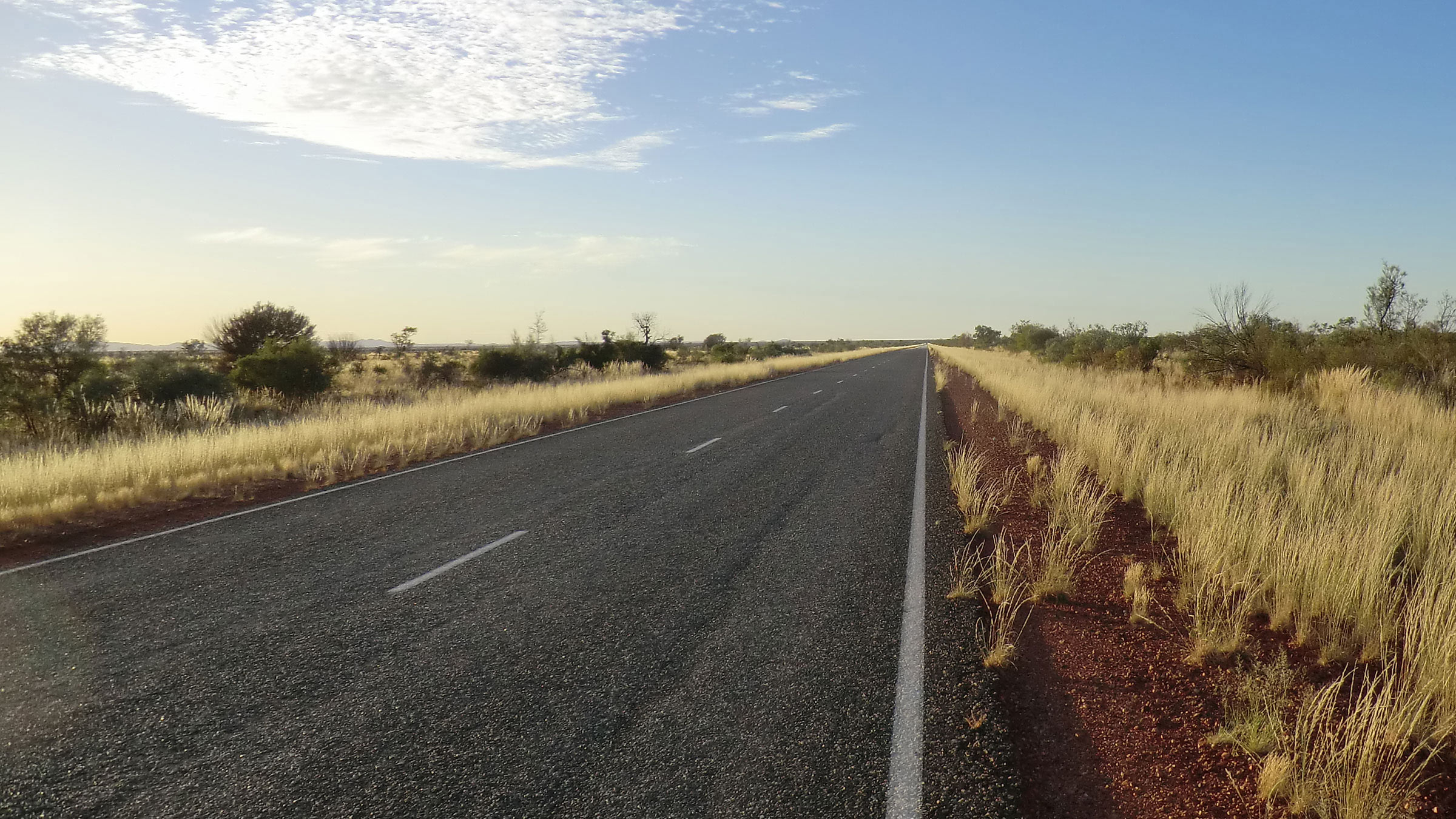 An empty road leading through the australian outback.