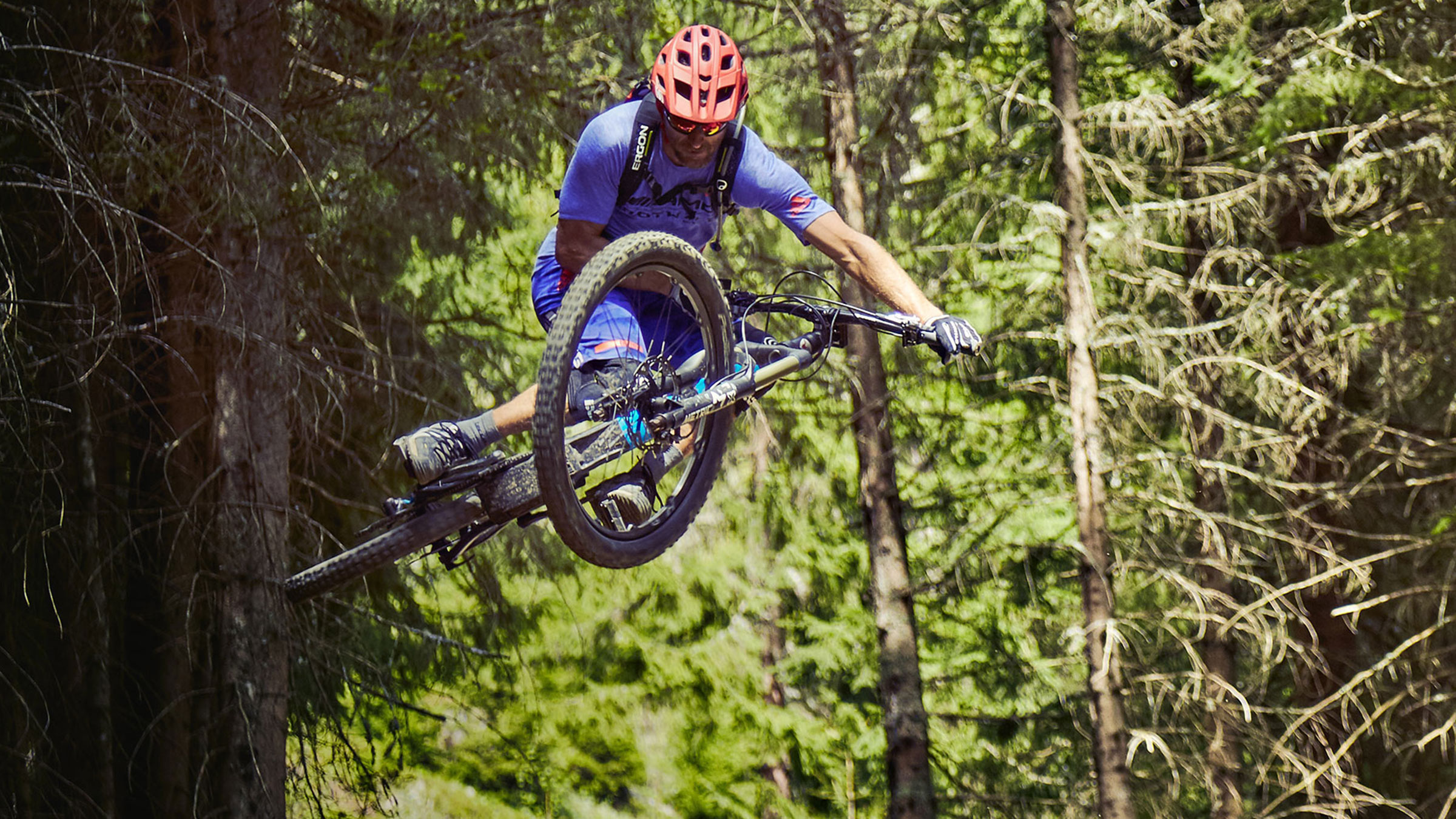 Richie Schley mid-ar during a jump in a forest.